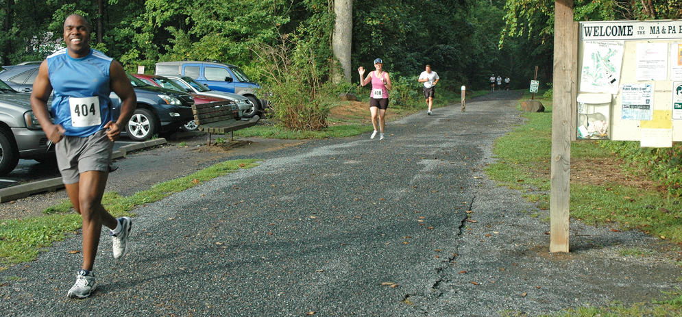 Two runners approaching end of BelAir trail, one is smiling, one is waving
